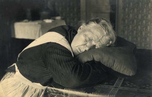 1738002 - Portret van een slapende vrouw. Frits Robben (1897-1971) fotografeerde zijn slapende moeder Dien, Gerardina Dominicus (1864-1949). Ze zit aan tafel met haar hoofd rustend op een kussen.