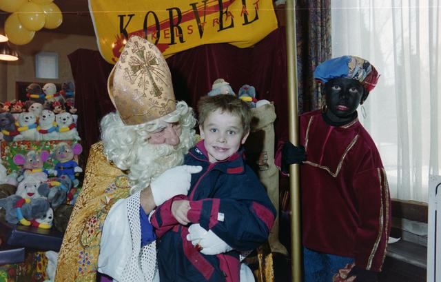 1237_001_003_020 - Feest. Korvel Winkelstraat. Sint Nicolaasviering. Een kind poseert met Sinterklaas en Zwarte Piet tijdens een Sinterklaasfeest georganiseerd door winkeliersvereniging Korvel Vooruit op 27 november 1999. Op de achtergrond staan de cadeautjes.