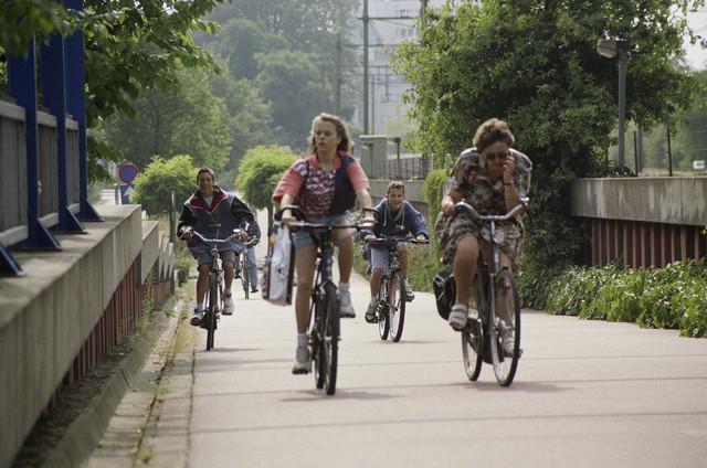 TLB023000726_002 - Straatbeeld. Fietsers op een fietspad langs de spoorbaan Tilburg-Oisterwijk. Vrouw met mobiele telefoon !