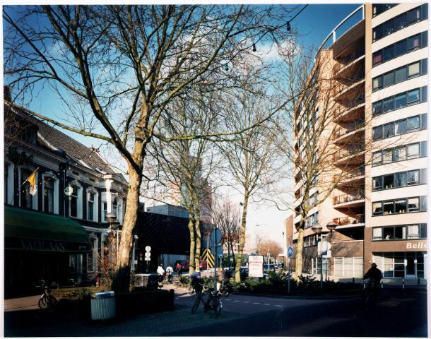 033372 - Tivolistraat gezien vanaf de Heuvel. Rechts het appartementengebouw Belle Vue, genoemd naar een café-restaurant dat vroeger ter plaatse stond. Achter de bomen 013, op de achtergrond het Interpoliscomplex.