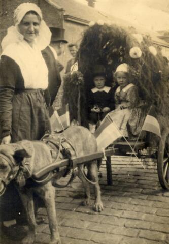 """601017 - De hondenkar, waarmee Jacq Vissers een """"eere-diploma"""" verdiende in de historische en allegorische optocht, georganiseerd door wijkvereniging Koningshoeven en omgeving, ter gelegenheid van de feestelijke herdenking van de stichting van """"de Hoeven"""" door de prins van Oranje (Willem II) in 1832. In de kar Leo en Thea Vissers. Naast de hond hun tante Jana van Gestel-Kouwenberg. Zij draagt de Brabantse muts uit de Meierij."""