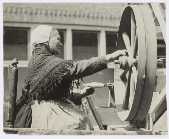 037449 - Textiel. Mieke Mutsaers, afkomstig uit de wijk Hasselt, in actie als spoelster in een folklorestoet eind juli 1929