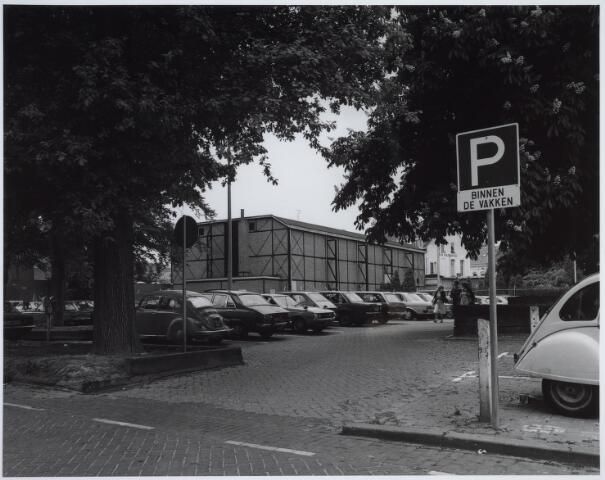 025446 - Parkeerterrein aan de Langestraat. In het midden de achterkant van de Harmonie-bioscoop