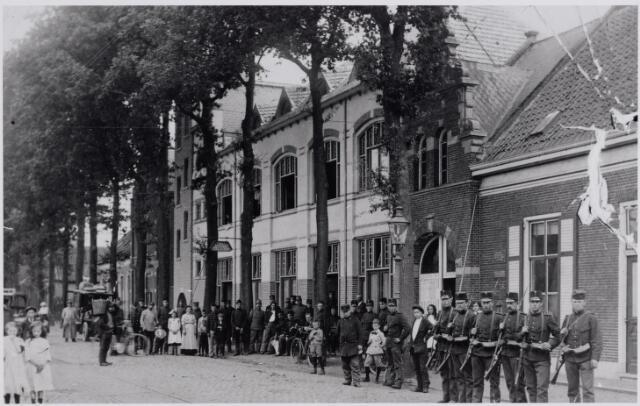 045618 - De Tilburgseweg tijdens de Eerste Wereldoorlog. In het midden café De Nijverheid van de familie Ever -Oosterlee. Op de foto groepen in Goirle ingekwartierde militairen.