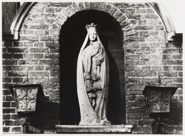 """067946 - Terracotta MARIABEELD van Louis MANIË (Den Bosch 1924). Lokatie: nis boven het poortje op het Korvelplein. Maria is hier uitgebeeld als beschermvrouwe van de jeugd. Het beeld is een variant op de zgn.""""Mantelmadonna"""". Aanvankelijk stond het ergens bij een kruispunt in de parochie Korvel. Trefwoorden: kerkelijke kunst, openbare ruimte."""