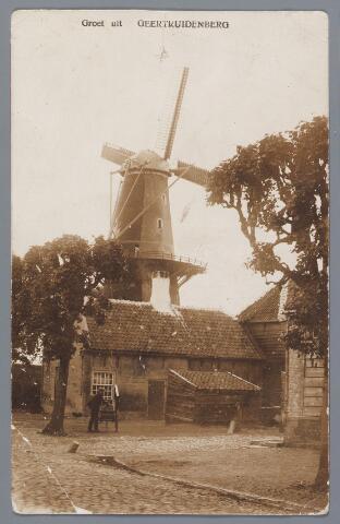 058178 - Deze stenen windkorenmolen  en rosmolen werd in 1714 gebouwd; de eigenaar was toen Alphons van Riel. Op de voorgrond de Venestraat, het straatje rechts in het Meistraattje en links onder het begin van het Molenpad