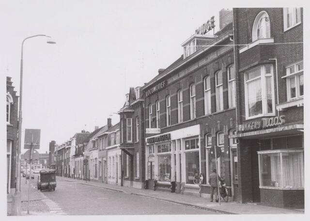 018227 - Emmastraat in de richting van het Piusplein omstreeks 1968. Rechts de winkels van Maas (drukkerij), Schlappi (ijzerwaren) en Van Asten (rijwielen)