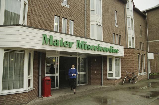 """TLB023000226_001 - Entree van woonzorgcentrum. Mater Misericordiae is van oorsprong een kloosterverzorgingshuis van de Zusters van Liefde van O.L.V. Moeder van Barmhartigheid. Het gebouw werd op 11 mei 1984 officieel geopend. Sinds januari 2009 staan de deuren ook open voor """"leken""""."""