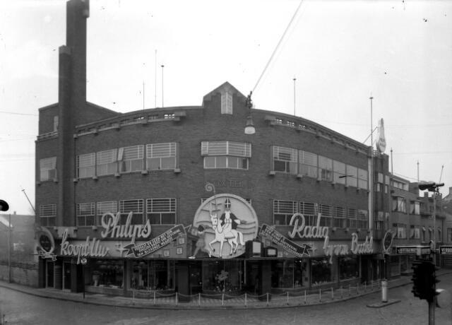 650449 - Schmidlin. De firma van Boxtel NV aan de Raadhuisstraat 1, de huidige Heuvelstraat 126. Naast een opvallend grote reclame voor Philips radio's zijn het pand en de etalages uitvoerig versierd voor Sinterklaas. Eind jaren veertig.