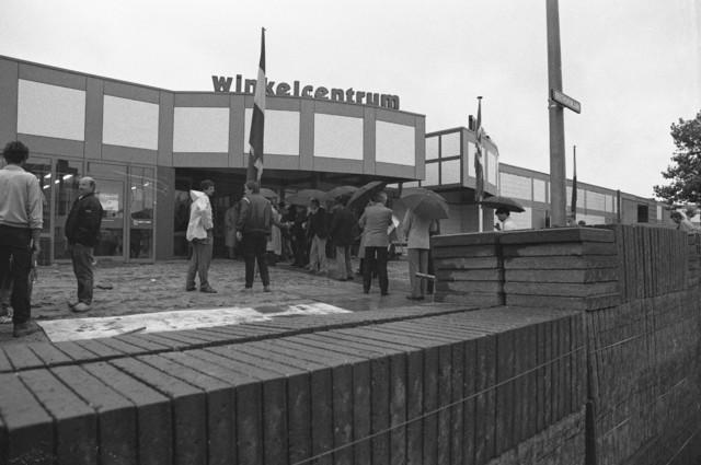 TLB023002537_003 - In de regen verzameld bij het Winkelcentrum Wagnerplein