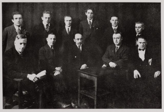 041080 - vakbeweging. Het werk van de commissie tot ontwikkeling en ontspanning van R.K. georganiseerden uit de R.K. werkliedenvereniging te Tilburg.  De toneelclub onder de werklozen, links met boekje de heer Jo Maessen (leider).