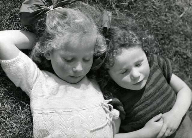 """602828 - Jaren '50. """"Moegespeeld""""; twee meisjes rusten uit in het gras."""