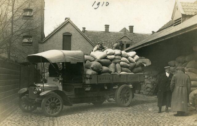 200450 - Binnenterrein van meelfabriekfirma A.C van Loon aan de Tuinstraat met vrachtwagen. De firma werd opgericht in 1883 door Augustinus Christianus van Loon, een molenaarszoon uit Lage Mierde. Op 24 september 1896 werd de meelhandel van de Spoorlaan verplaatst naar de Tuinstraat. Eind 1925 werd de firma A.C. van Loon ontbonden en voortgezet door zoon Leon onder de naam N.V. A.C. van Loon Graan- en Meelbedrijf te Tilburg. In de jaren dertig verplaatste de firma haar bedrijf van de Tuinstraat naar de Piushaven.