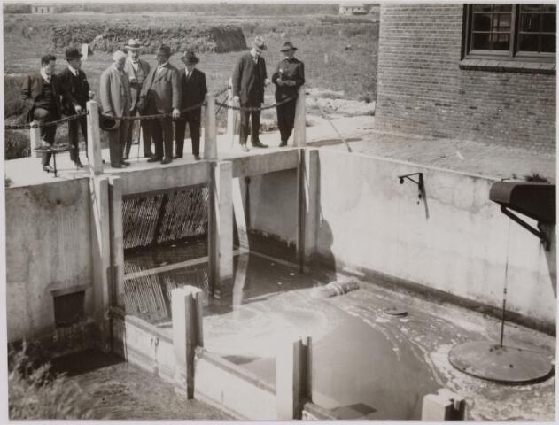 040840 - Werklozen voorzieningen. In de werkverschaffing te Tilburg worden werklozen tewerk gesteld in diverse projecten (1927) Foto: Bij het bassin, waarin het vuile water vóór 't oppompen opgevangen wordt, na een rooster gepasseerd te zijn, waarvoor de mede gevoerde stukjes hout en grove vuildelen worden vastgehouden. De vuile vetlaag ziet men drijven.(Loon op Zandseweg) (Bij het bezoek van Minister Kan aan de gemeentelijke werkverschaffing op 20 mei 1927)