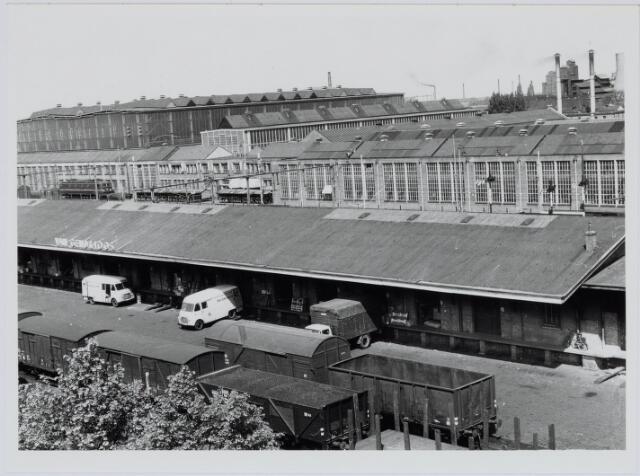037098 - Spoorwegen, Goederenemplacement, N.S.: Voormalige goederenloods en los- en laadweg langs de spoorlaan omstreeks 1959. Op de achtergrond de Centrale Werkplaats van de Nedrelandse Spoorwegen.