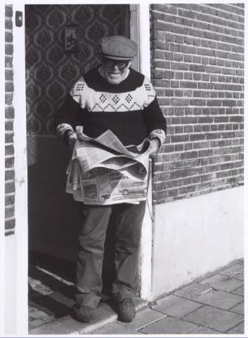016755 - Bewoner olieboer Speijers van het pand Buitenstraat 5 leest een krant in de deuropening.