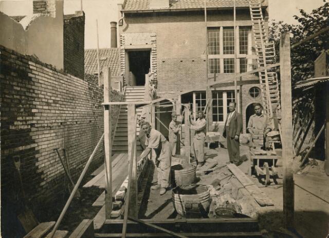 601945 - De bouw van het nieuwe fotoatelier van Leo van Beurden in de tuin van de Willem II-straat 39.  In 1938 werd het oude fotoatelier van hoffotograaf Van Beurden gesloopt en vervangen door een modern ontwerp van architect Jos Bedaux. Het oude atelier stond in de tuin van het pand aan de Willem II-straat 39 te Tilburg. Het nieuwe atelier werd iets naar achteren geplaatst en kreeg de voorgevel aan de Telexstraat. Er was ook een ingang vanaf de Willem II-straat 39. Jos Bedaux heeft duidelijk rekening gehouden met de bestemming van het pand. Door de grote ramen had de studio van leo van Beurden veel daglicht.