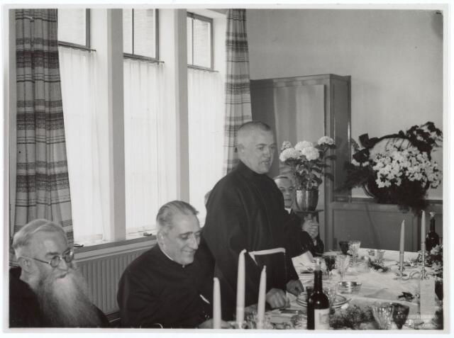 016494 - De broeder-overste van klooster Mariahof van de Broeders Penitenten spreekt de aanwezigen toe bij aanvang van het diner ter gelegenheid van de officiële inzegening. Links naast hem pastoor Klijn