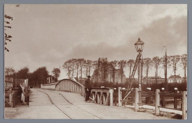 """058090 - De voetbrug aan de Veerse zijde. De Tankfabriek is nog niet gebouwd op de reeds geslechte vestingwal aan de Donge. De wal werd in 1913 geslecht en de Tankfabriek, toen en veel later ook nog """"de Naadloze"""" genoemd, werd gebouwd in 1914. De brug had aan de Veerse zijde een rolgedeelte om het scheepvaartverkeer mogelijk te maken, daarom werd de brug ook wel rolbrug genoemd."""