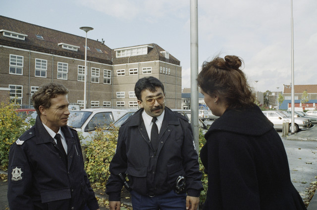 TLB023000254_003 - Twee politieagenten met een mevrouw op een parkeerterrein gelegen achter de voormalige Hogere Textielschool. Foto is gemaakt in het kader van de Gemeentelijke Begrotingsspecial 1993.