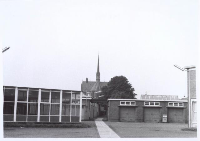 019441 - Texielindustrie. Binnenplaats van wollenstoffenfabriek H.F.C. Enneking aan de Goirkestraat. Links de personeelskantine en daarachter de ´kleine´ weverij. Rechts de garage. Op de achtergrond de kerk van de parochie Hasselt