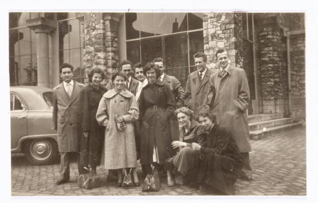 """038569 - Volt. Opleidingen. Deze foto is gemaakt voor de z.g.n. """"steentjeskerk"""" in Eindhoven. De dames en heren reisden in die tijd gezamenlijk per trein naar de Philips Bedrijfsschool in Eindhoven. De dames volgden een opleiding technisch tekenen en of calqueuse, de heren een andere hogere technische opleiding. Hurkend v.l.n.r.: Edith de Jong en Corry Lijs. Staand v.l.n.r.: Hein Quinten, Diny Weyers, Rietje Maas, Piet van de Ven, Cees Staps, Jetty de Witte, nog juist zichtbaar Ton van Vugt, Jan van Iersel en Fer van Weereld. De foto is rond 1960 genomen.   Voorbijganger met toestel van een van de leerlingen."""
