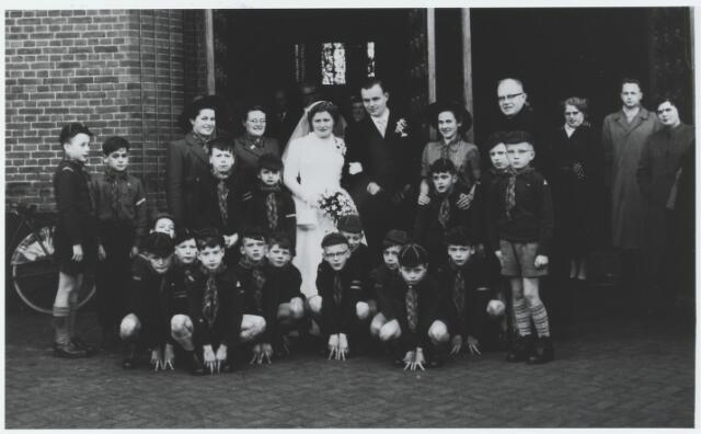 056293 - Welpen van de St. Willebrordusgroep te Goirle bij de St. Janskerk ter gelegenheid van het huwelijk van welpenleidster Bep Schalkwijk met Jos van Gils. Links van de bruid de welpenleidsters Spanings en Witters. Rechts van de bruidegom welpenleidster Riet Vekemans-Vermeulen en kapelaan Frik.