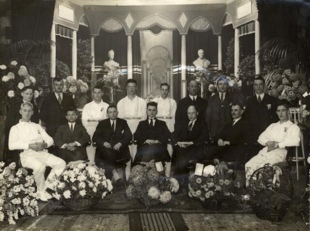 """092843 - Gymnastiekvereniging """"Kunst en Kracht"""" vierde haar 12 1/2 jarig bestaan in zaal Van Broekhoven aan het Smidspad. Op de foto het bestuur. Op de achtergrond de borstbeelden van de paus en koningin Wilhelmina."""