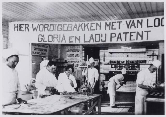 103728 - Tentoonstelling. I.B.A.T. tentoonstelling in de Kon. Harmonie stationsstraat (1930) Uiterst links dhr. Jansen. Hier wordt gebakken met van Loon's Gloria en Ladij patent.