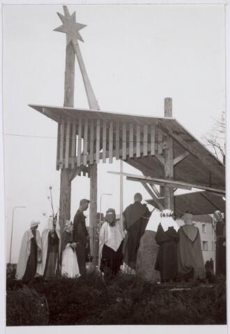 021484 - Religieuze rituelen. Kerststal op de Heuvel in 1966, gemaakt door de Tilburgse beeldhouwer Hans Claessen in de jaren `50. Driekoningenzangertjes brengen een bezoek aan het stalletje