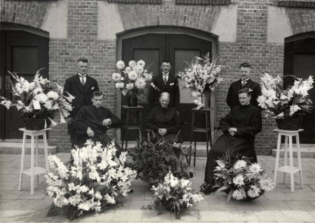 092882 - Foto genomen ter gelegenheid van het opdragen van de eerste H. Mis door Waltherus Johannes van den Hout, pater in de congregatie van de H. Geest. Hij werd geboren te Tilburg op 23 mei 1909 en overleed te Weert op 23 september 1966. In het midden zijn moeder, Cornelia Verbunt, geboren te Gilze-Rijen op 23 december 1864, dochter van Joannes Verbunt en Hendrica de Swart en weduwe van bosarbeider Cornelis van den Hout, die geboren werd te Alphen en Riel op 27 mei 1861 als zoon van Adriaan van den Hout en Elisabeth van Gestel. Cornelis van den Hout overleed te Tilburg op 17 juni 1923. Links van Cornelia Verbunt de neomist, Waltherus van den Hout, rechts broeder Martinus Adrianus van den Hout, geboren te Tilburg op 11 november 1905, lid van de congregatie  van de missionarissen van het H. Hart MSC. Staande v.l.n.r.: Johannes Franciscus van den Hout, geboren te Gilze-Rijen op 18 september 1894 (getrouwd met Cornelia Johanna Jansen), Adrianus van den Hout, geboren te Gilze-Rijen op 29 september 1891 (getrouwd met Regina Antonia Verhoof)  en Deonisius Petrus van den Hout, geboren te Gilze Rijen op 13 maart 1897 (hij trouwde Regina C.J. Schoenmakers). Een broer, Antonius Wilhelmus van den Hout, geboren te Tilburg op 10 oktober 1903, was een jaar eerder, op 22 november 1934 te Tilburg overleden.