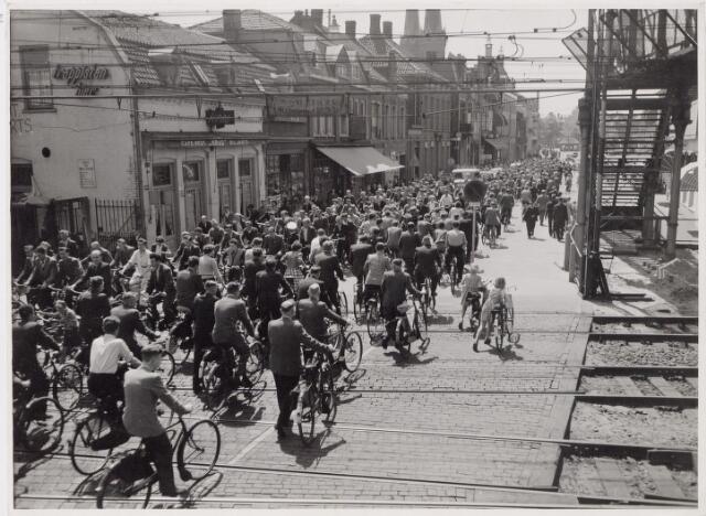 045239 - Spoorwegen: Massa fietsers passeren de Spoorwegovergang Heuvel-Koestraat. Op de achtergrond de Heuvel.