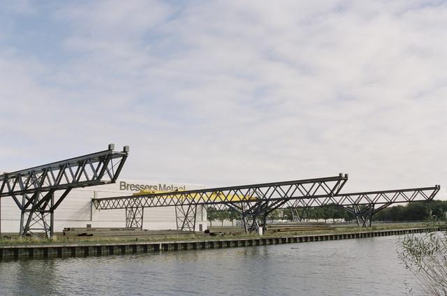 TLB023000975_001 - Bedrijfspand Bressers Metaal aan de Apolloweg, gezien vanaf de overkant van het Wilhelminakanaal op het Moerse Pad.
