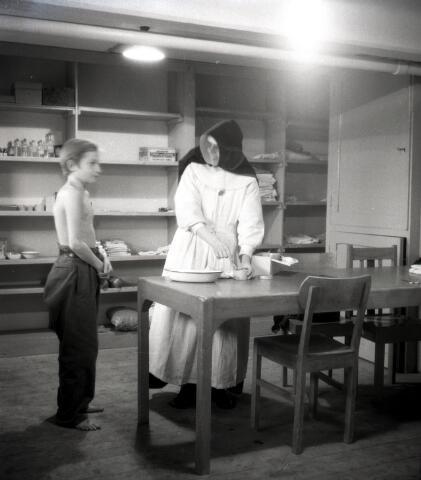 650643 - Gezondheidszorg. Een evacué uit de Betuwe wordt gekeurd in een noodziekenhuis in de Leo XIII-school door een zuster Franciscanes. In verband met de komst van veel Betuwse evacués werd het oorlogscomité opgericht, omstreeks 1944-1945.