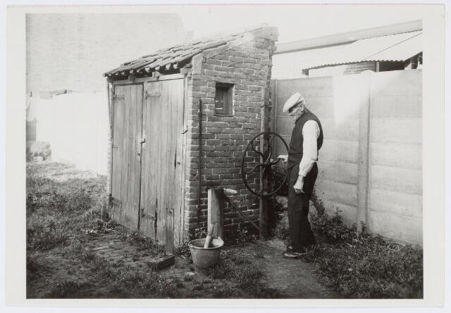 037447 - Textielnijverheid. Frans van Geloven, de laatste thuiswever van Tilburg, bezig met het spoelen van de wol op de plaats achter zijn huis in de Tongelose Hoefstraat.