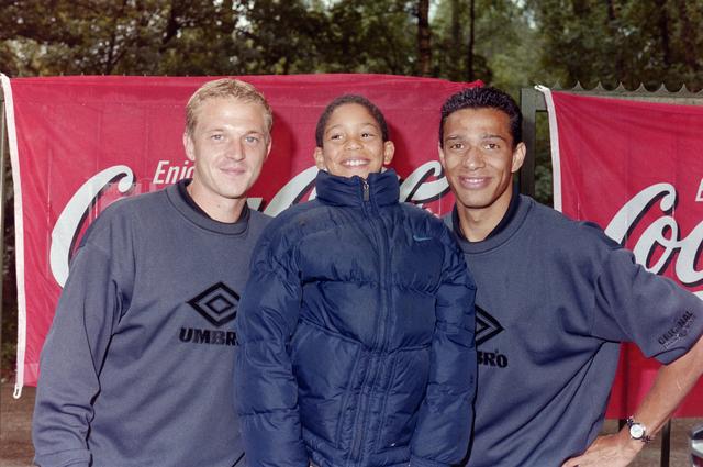 1237_001_031_007 - Sport. Voetbal. Willem II promotour. Spelers Dimitri Shoukov (links) en Raymond Victoria (rechts) poseren met een supporter op 1 augustus 2000.