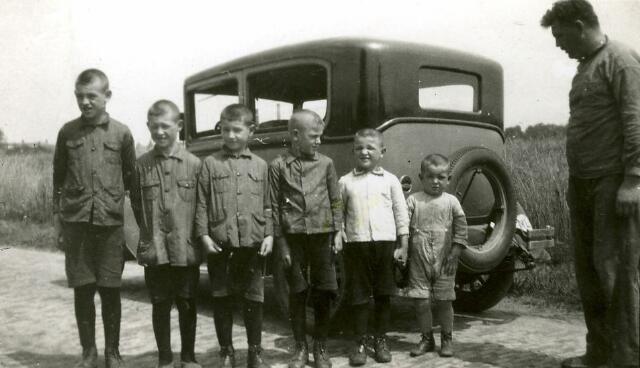 """082715 - 'Molenaar Theeuwes met 6 jonge mulderkes'  Op de foto de kinderen uit het eerste huwelijk van Hubertus Johannes (Bart) Theeuwes, molenaar in Ulicoten. Het zijn (v.l.n.r.) Victor, Sjaak, Jan, Jos, Harrie, Frans en To.  De kinderen hebben """"doordeweekse' kleren aan. De auto op de achtergrond is een Willy 'Whippet' uit 1929."""