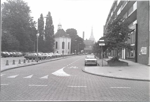 021873 - Heuvelstraat gezien vanuit de Schoolstraat in de zomer van 1983. Links de Nederlands Hervormde Pauluskerk en rechts winkels aan de Schouwburgring. Op de achtergrond de toren van de Heikese kerk