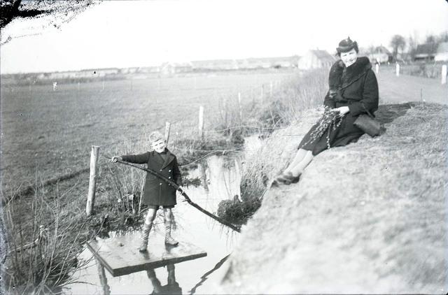 651583 - Vrouw zittend op een dijk en kind op een vlot op het water tussen de landerijen. De Bont. 1914-1945.