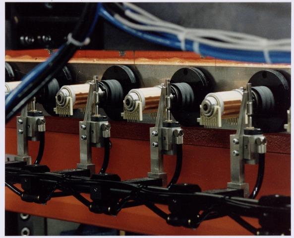 038985 - Volt. Noord. Productie of fabricage van lijntransformatoren, ook wel genoemd lijntrafo`s of LOT ( Line Output Transformers ). Hier een detail van een meervoudige wikkelautomaat met daarop de producten. De vermoedelijke datum 1985. Lijntrafo's wekten de hoge spanning op (25.000 volt) die nodig was om een televisiebeeld tot stand te brengen.