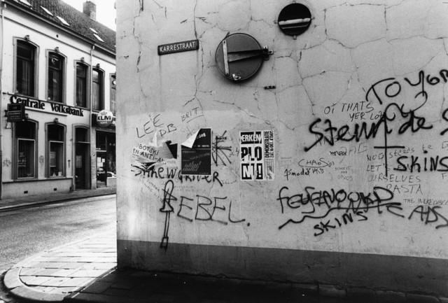 """1238_F0322 - Gebouw met graffiti en aanplakposters aan de Karrestraat. Overkant: Pand """"Centrale Volksbank""""."""