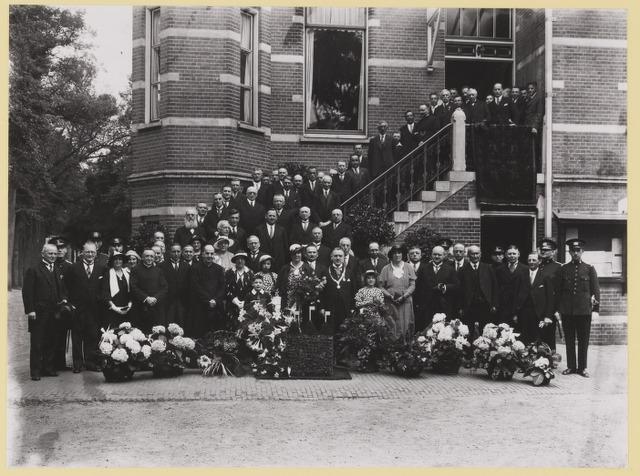 077236 - Voorzijde van het oude raadhuis met vele gasten op de trappen en daarvoor ter gelegenheid van . . . ? met een van bloemen gemaakt wapen van Oisterwijk op de voorgrond.