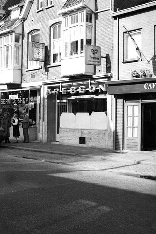 1237_012_925-1_034 - Exterieur winkels Korvelseweg, Bresson (juwelier) en de service shop (onderdelen speciaal zaak). Lambertus Bresson was bediende van Joseph Holtschneider, in 1901 nam hij de zaak over en begon een een winkel aan de Gasthuisring. Hij was gespecialiseerd in het repareren en verkopen van klokken. Zijn zoon Henri opende in 1955 een zaak aan de Korvelseweg. De zaak verhuisde nog naar de Heuvelstraat maar in 2008 ging de juwelierszaak failliet.