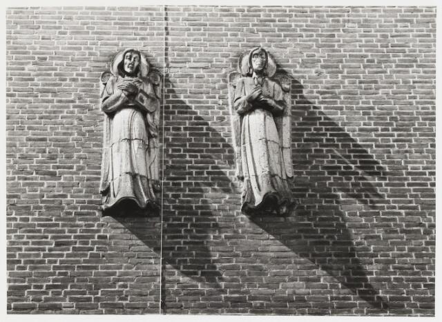 """067672 - WO2 ; WOII ; TWEE ENGELEN van de LImburgse beeldhouwer Charles EIJCK (Meerssen 1897 - Nuth 1983). Lokatie: gevel van de R.K. Basisschool """"Armhoefse Akkers"""", Spoortdijk 68, zijde Armhoefstraat. Kort voor de Tweede Wereldoorlog kreeg Charles Eijck de opdracht om uit de reeds in het priesterkoor van de Sacramentskerk aanwezige brokken tufsteen, engelenfiguren te hakken. Nadat hij tot tevredenheid van de pastoor een eerste serie van vier engelen had vervaardigd, kwam het bij een vervolgopdracht tot onenigheid tussen Charles Eijck en zijn opdrachtgever: de eerste twee beelden van deze nieuwe reeks konden de pastoor niet bekoren. Ze werden uit de muur verwijderd, waarna de opdracht gegund werd aan de Tilburgse kunstenaar Frans Mandos (1910-1977). De twee in ongenade gevallen engelenfiguren werden in 1955 aangekocht door het bestuur van de lagere school in de Sacramentsparochie met het oogmerk om de beelden te verwerken in de gevel van de nieuw te bouwen school. Dat gebeurde wellicht op voorstel van Charles Eijck die op dat moment al betrokken was bij de decoratieve aankleding van het nieuwe schoolgebouw. Foto 1985  Trefwoorden: Kunst in de openbare ruimte. Onderwijs."""
