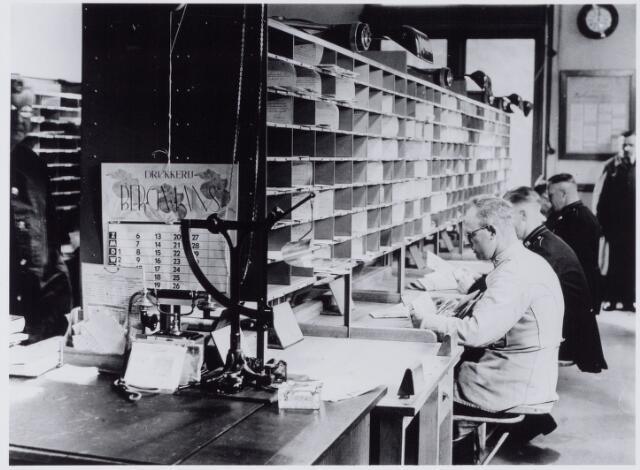 050012 - Foto uit ´Je Taalboek´ van frater Victor van Nispen. Interieur van het Post- Telefraaf- en Telefoonkantoor aan de Telegraafstraat 39. Tegen de kast een kalender van de Tilburgse drukkerij Bergmans.