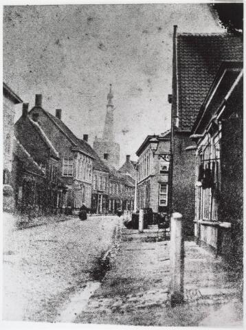 021680 - De oudste foto van de Heuvelstraat, daterend van omstreeks 1880. Deze verbindingsweg tussen de kernen van de herdgangen Kerk en Heuvel werd als eerste in het dorp bestraat en heette toen voor lange tijd Steenweg. Het werd de deftigste straat van Tilburg en op het einde van de 19e eeuw ook dé winkelstraat bij uitstek. Rechts, met de parapluutjes als uithangteken, de sedert 1853 bestaande zaak van Jean-François Gimbrère