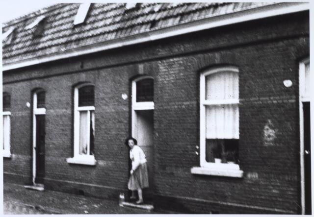 024455 - Een vrouw zetmelkflessen buiten voor haar deur in de Korte Schijfstraat