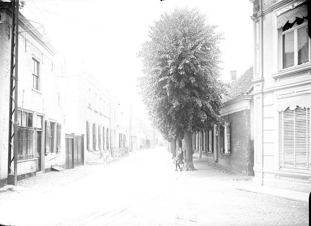 095044 - Dorpsbeelden Made. Overbelicht glasnegatief met een straatgezicht. Een man of jongen leunt tegen een boom.