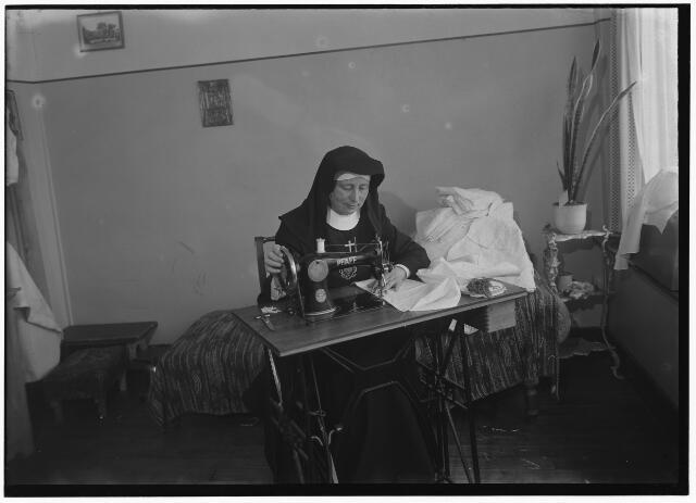 050990 - Moeder overste van het St. Jacobusklooster van de zusters van het Allerheiligst Hart van Jezus (zusters van Moerdijk) aan de Broekhovenseweg 166 aan de naaimachine. Het klooster staat op de hoek van de Ringbaan-Zuid. Na het vertrek van de zusters woonden er leden van de congregatie der oblaten van St. Franciscus van Sales.