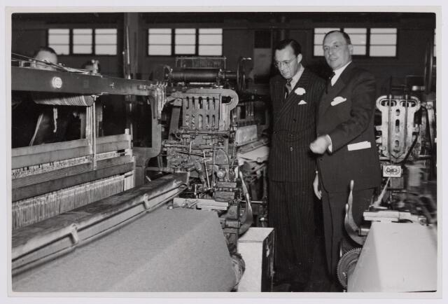 037658 - Textiel. Prins Bernhard wordt op 13 november 1950 rondgeleid in wollenstoffenfabriek H. F. C. Enneking. Hier is het gezelschap in de weverij. Het bedrijf had twee weverijen, een zogenaamde ´grote´ en een ´kleine´. Deze foto is genomen in laatstgenoemde